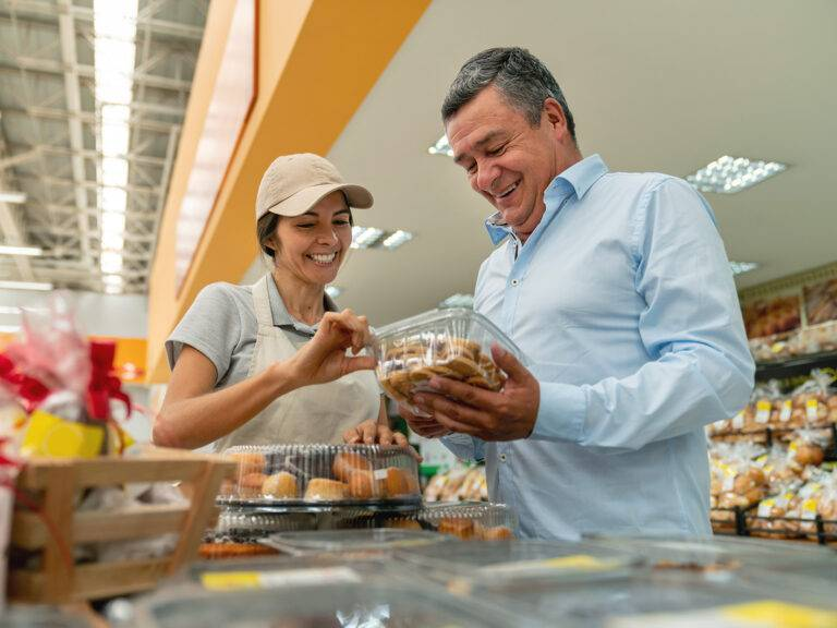 Friendly sales woman offering delicious cookies at the bakery section to male customer