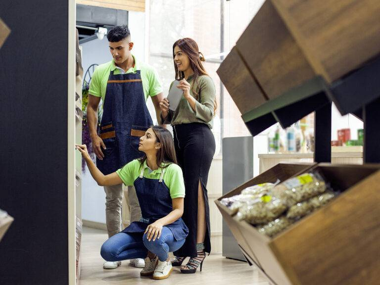 Two supermarket workers and one customer standing infront of a shelf
