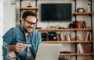Handsome man with laptop and credit card at home, portrait.