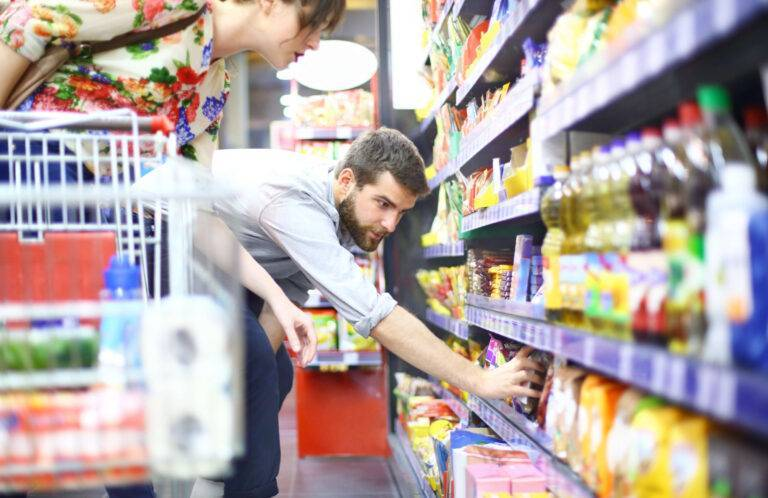 Man picking up some products from the supermarket shelf
