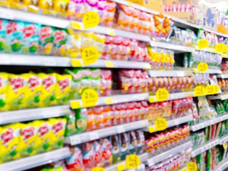 Blurred fast food snacks for sale on supermarket shelf.