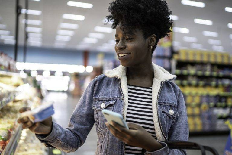 Young woman using phone and choosing products in supermarket