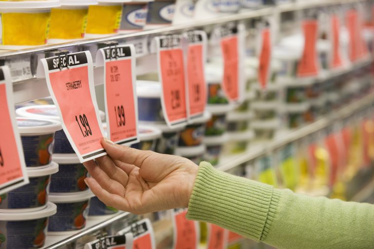 Checking price of item in supermarket aisle